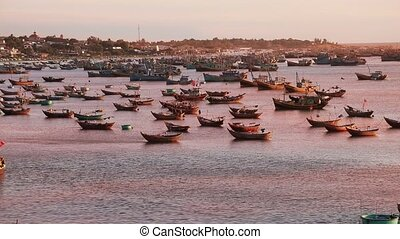 Fishing ships at sunset in Mui Ne, Vietnam - The bay with...