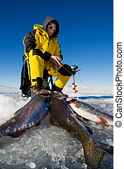 Fishing success - Ice fisherman with his catch of rainbow...