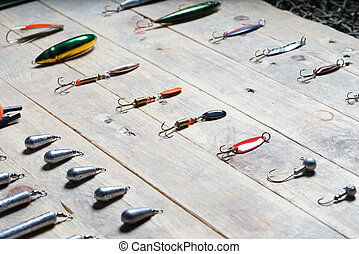Fishing tackles on the wooden background.