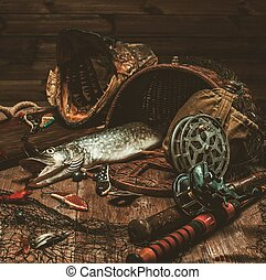 Fishing tools and fresh pike on a wooden table