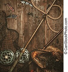 Fishing tools and pike's head on a wooden table