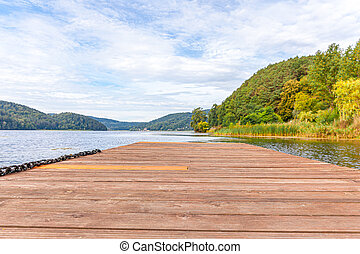 Fishing tourism relax concept. Beautiful forest lake or river on sunny summer day and old rustic wooden dock or pier. Fishing bridge on morning lake.