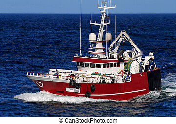 Fishing Trawler underway at speed over blue sky and sea.