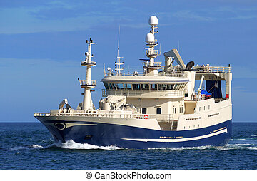 Modern Fishing vessel underway over blue sky and sea.