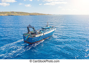 Fishing vessel boat floating in the blue sea along the coast.