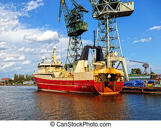 Fishing vessel trawler in a repair yard.