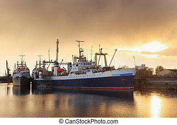 Fishing vessels in the port on the background of a sunset.