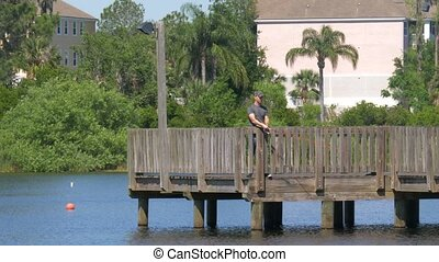 Fishing with spinning tackle on wooden pier. Fisherman cast...