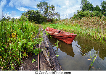 Fishing wooden boat at the lake in summer day