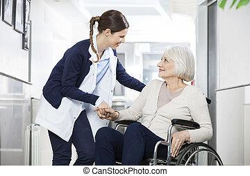fisioterapeuta, mulher, consolar, cadeira rodas, sentando, sênior