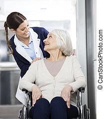 fisioterapeuta, olhar, sênior, paciente, sentando, em, cadeira rodas