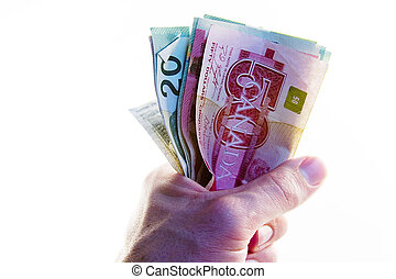 A male hand holding a tight wad of Canadian money.