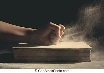 Fist on an old book. - A fist pounding down on an old book ...