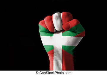 Fist painted in colors of basque flag - Low key picture of a...