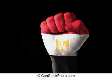Low key picture of a fist painted in colors of egypt flag