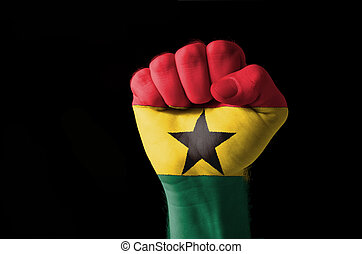 Low key picture of a fist painted in colors of ghana flag