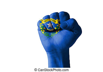 Low key picture of a fist painted in colors of american state flag of nevada