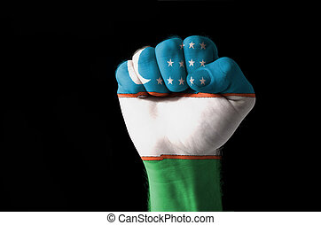 Fist painted in colors of uzbekistan flag