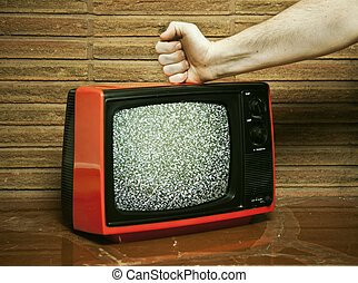 Fist smashing a TV - A mans fist is hitting a static filled...