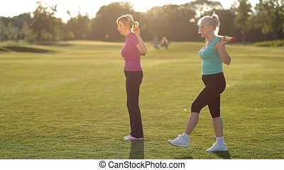Fit adult women doing forward lunges with body bar - Lovely...
