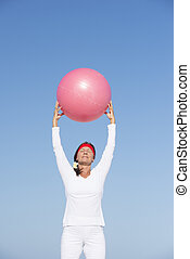 Fit and active senior woman exercising with ball