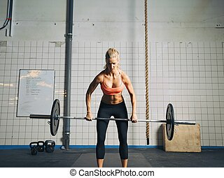 Crossfit woman lifting heavy weights in gym