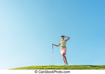 Fit and cheerful woman during practice on the green grass of a p