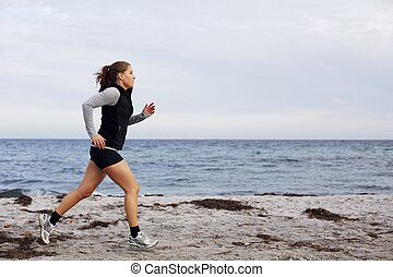 Fit and healthy young woman running along shoreline. ...