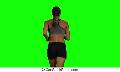 Fit and muscular woman jogging. Back view. Green screen