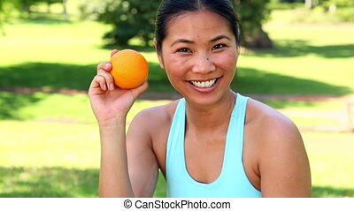 Fit asian girl showing an orange