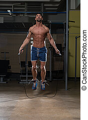 Fit Athlete Is Jumping Rope - Young Man In Gym Is Jumping ...