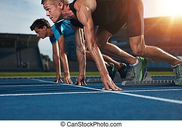Fit athlete running race in athletics racetrack on a sunny...