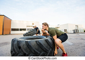 Fit Athletes Doing Tire-Flip Exercise - Fit male and female...
