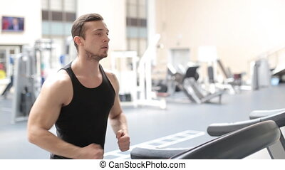 Fit athletic man is starting to run on the treadmill in the sport gym