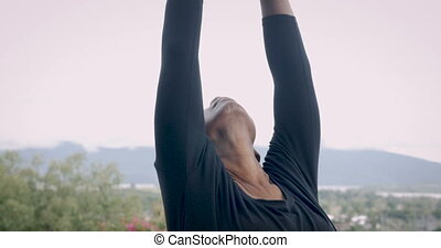 Fit athletic senior woman stretching her spine outdoors with...