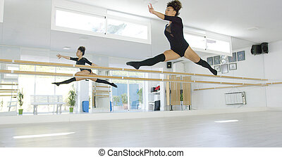 Fit athletic young dancer leaping in the air