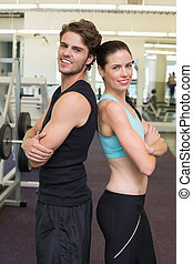 Fit attractive couple smiling at camera at the gym