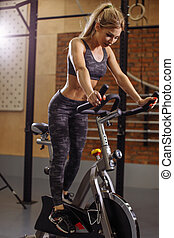 fit attractive girl training on the exerise bike