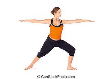 Fit attractive young woman practicing yoga exercise called Warrior Pose 2, sanskrit name: Virabhadrasana 2, this posture strengthens and stretches legs, ankles, groins, chest, lungs and shoulders