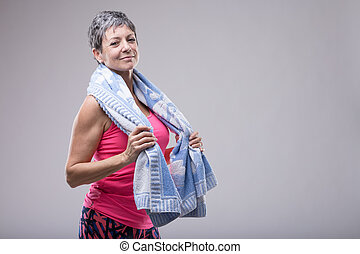 Fit attractive woman with a towel around her neck