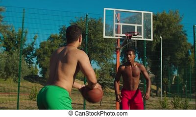 Muscular build african basketball defender jumping to block shot, deflecting field goal attempt from offensive player to prevent score while playing streetball game on outdoor court in morning.