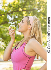 Fit blonde holding green apple