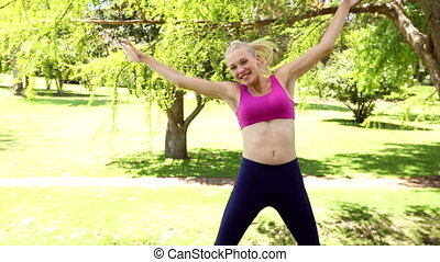 Fit blonde jumping and smiling