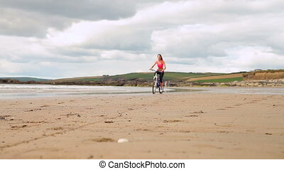 Fit brunette biking on the beach on a clear day