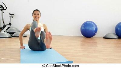 Fit brunette doing pilates