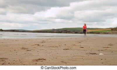 Fit brunette running on the beach