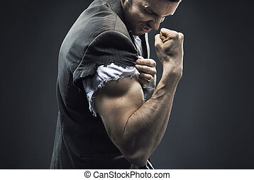 Fit businessman making the muscles