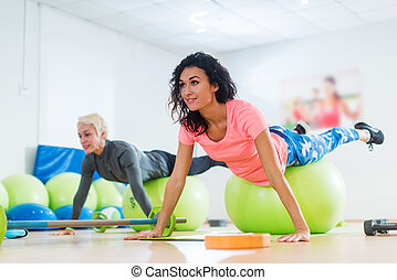 Fit Caucasian female athletes in sportswear doing Pilates...