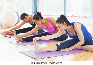 Fit class stretching legs on mats at yoga class in fitness...