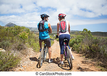 Fit couple about to cycle on mountain trail on a sunny day